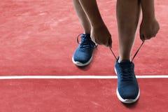 Человек связывая ботинки бега на гоночном треке стоковые изображения