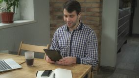 Человек сидит на таблице с таблеткой, наушниках в ушах, говорить онлайн стоковая фотография