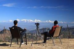 Человек 2 сидя перед могущественными Гималаями на празднике стоковая фотография rf
