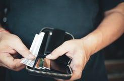Человек смотря банкноту долларов в бумажнике cash деньги и shoping руки человека с бумажником Селективный фокус стоковое изображение