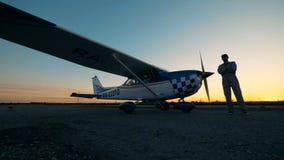 Человек стоит на взлетно-посадочной дорожке около небольшого самолета, конца вверх акции видеоматериалы