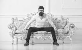 Человек с бородой и усиком тратит отдых с книгой Лектор сидит на софе и владения записывают, белая предпосылка стены self стоковые фото