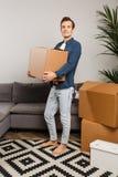 Человек с картонной коробкой в руках на предпосылке серой софы, крытых заводов стоковое фото rf