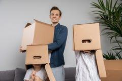 Человек с картонной коробкой, детьми с коробками на голове стоковые изображения rf