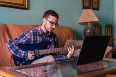 Человек учит играть электрическую гитару дома стоковое изображение rf