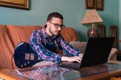 Человек учит играть электрическую гитару дома стоковая фотография