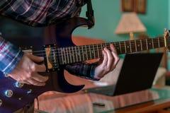 Человек учит играть электрическую гитару дома стоковые изображения