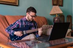 Человек учит играть электрическую гитару дома стоковые фотографии rf