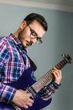 Человек учит играть электрическую гитару дома стоковое изображение