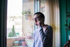 Человек разговаривая с концом телефона вверх по окну стоковое фото rf