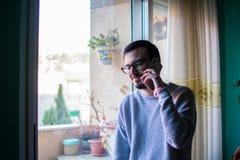 Человек разговаривая с концом телефона вверх по окну стоковое изображение