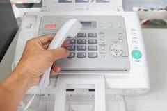 Человек руки использует факс для отправки бумаги в офисе стоковые фото