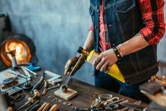 Человек moxing различные металлы на рабочем месте стоковые изображения rf