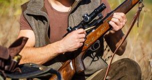 Человек охотника Охотиться период Мужчина с оружием, винтовка Человек поручает винтовку звероловства конец вверх Процесс зверолов стоковое изображение rf