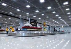 Чемодан людей ждать на конвейерной ленте багажа на заявке багажа в аэропорте Бангкоке Suvarnabhumi стоковые фото