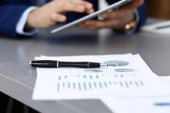 Черная ручка лежа над бумагами аналитика дела Руки бизнесмена используя планшет на предпосылке стоковые изображения