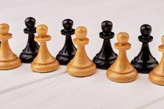 Черные и коричневые пешки шахмат стоковые изображения