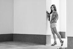 Черно-белый полнометражный портрет красивой счастливой молодой женщины брюнета в положении непринужденного стиля и полагаться на  стоковое изображение