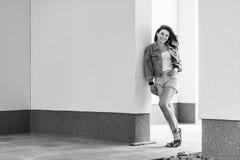 Черно-белый полнометражный портрет красивой счастливой молодой женщины брюнета в положении непринужденного стиля и полагаться на  стоковые фотографии rf