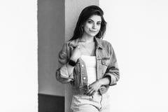 Черно-белый портрет красивой молодой женщины брюнета в положении непринужденного стиля и полагаться на стене, положении, держа ее стоковые изображения