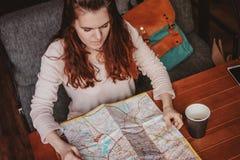 Чтение путешественника девушки молодой женщины красное главное смотря бумажную карту в кафе стоковое фото rf
