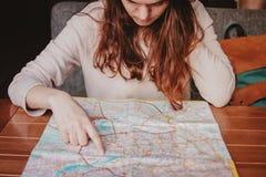 Чтение путешественника девушки молодой женщины красное главное смотря бумажную карту в кафе стоковое изображение