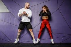 Худенькая красивая девушка в одеждах спорт и сильный атлетический человек скачут на предпосылку стильной фиолетовой стены стоковая фотография