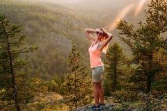 Худенькая молодая усмехаясь длинн-с волосами женщина в футболке и стойки шортов на горе летом Женщина на зоре в стоковое фото