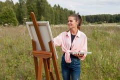 Художник красит изображение в поле стоковые изображения