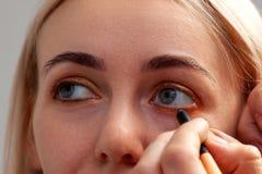 Художник макияжа с помощью карандашу в одной руке рисует стрелку на раскрытых глазах модели, с другими тягами руки стоковая фотография rf