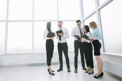 Работники обсуждают деловые документы стоя в лобби офиса стоковое изображение rf