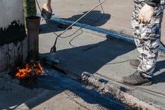 Работник устанавливая фольгу смолки на крышу здания Водоустойчивая система torching газа и огня стоковое изображение rf