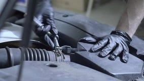 Работник обслуживания автомобиля вывинчивает болты под клобуком автомобиля Оно ремонтирует автомобиль, проверяет представление сток-видео