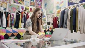 Работы молодой женщины на ноутбуке и беседа над смартфоном сток-видео