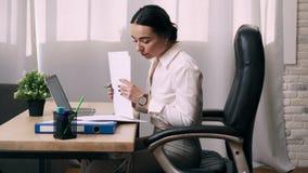 Работы молодой женщины с документами в офисе