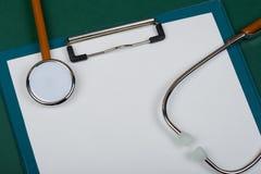 Рабочее место доктора - стетоскоп и пустая доска сзажимом для бумаги на предпосылке зеленой книги стоковые фотографии rf