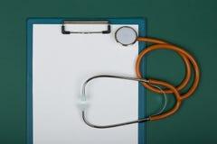 Рабочее место доктора - стетоскоп и пустая доска сзажимом для бумаги на предпосылке зеленой книги стоковые изображения rf