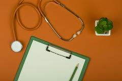 Рабочее место доктора - стетоскоп и пустая доска сзажимом для бумаги на оранжевой бумажной предпосылке стоковые изображения
