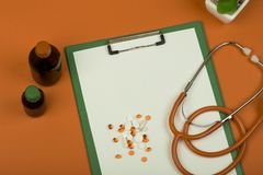 Рабочее место доктора - стетоскоп, таблетки, медицинские бутылки и пустая доска сзажимом для бумаги на оранжевой бумажной предпос стоковое фото