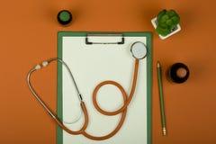 Рабочее место доктора - стетоскоп, таблетки, медицинские бутылки и пустая доска сзажимом для бумаги на оранжевой бумажной предпос стоковая фотография