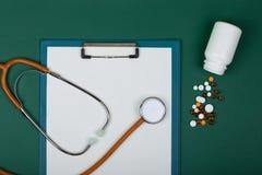 Рабочее место доктора - стетоскоп, таблетки, медицинские бутылки и пустая доска сзажимом для бумаги на предпосылке зеленой книги стоковая фотография