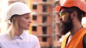Рабочий-строитель и инженер говоря на месте строительной площадки Работники в шлемах на строя области Мужчина и женщина сток-видео