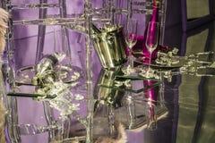Разбросанные стулья и стекла, бутылки шампанского экспозиция Декоративное шоу-окно Розовые цветы Необыкновенное решение беспорядо стоковая фотография
