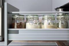 Различные семена в опарниках хранения в hutch, белой современной кухне в предпосылке Умная организация кухни стоковая фотография