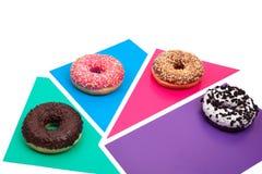4 различных donuts на ярком пестротканом взгляде сверху предпосылки стоковое изображение