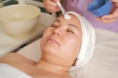 Размер плюс модель принимает косметические процедуры на салон красоты Щетка Beautician для приложения маски для стороны морщинок стоковые фотографии rf