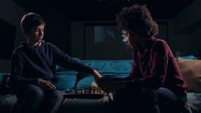 Разнообразная предназначенная для подростков игра законцовки шахматистов вечером сток-видео