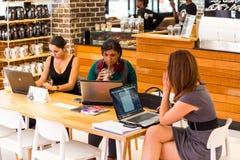 Разнообразные женские клиенты используя интернет в кофейне стоковое изображение rf
