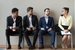 Разнообразные мужские кандидаты смотря интервью женского соперника ждать стоковое фото