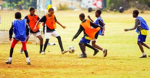 Разнообразные дети играя футбол футбола на школе стоковые изображения